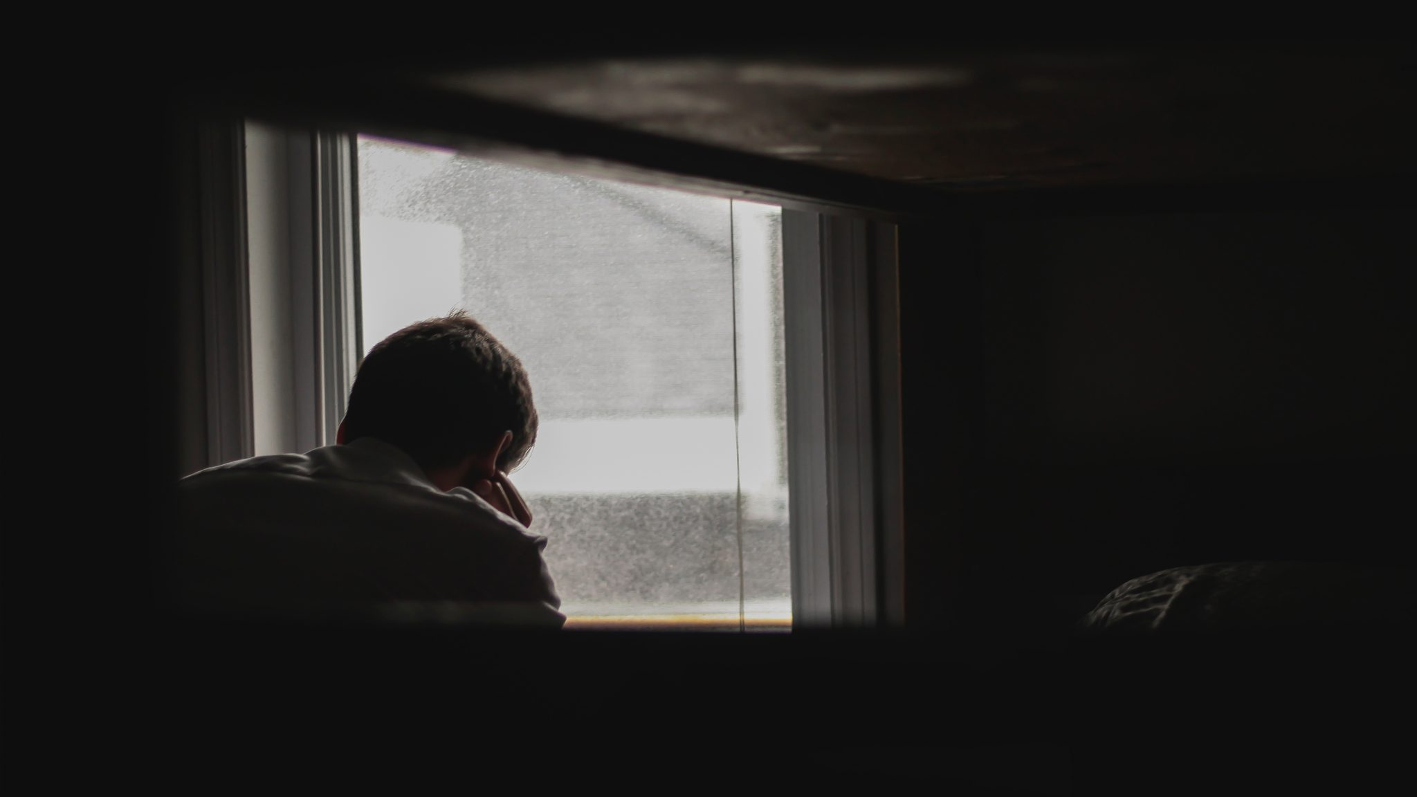 man looking outside by window